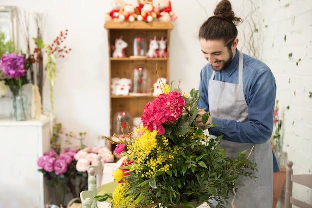 Glücklicher junger männlicher florist, der den schönen blumenblumenstrauß im blumenladen schafft