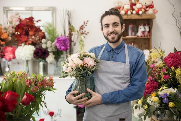 Glücklicher junger männlicher florist, der in der hand den blumenvase steht im blumenladen hält