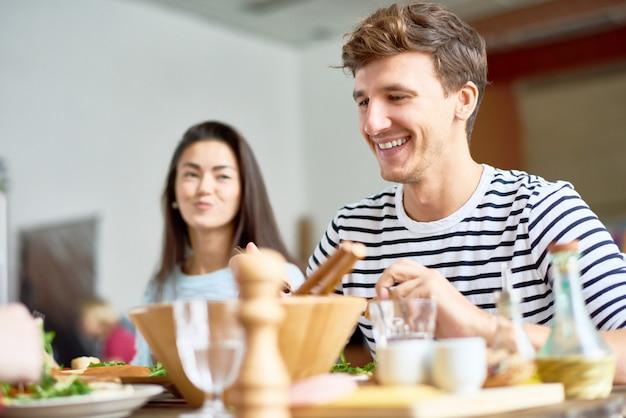 Glücklicher junger mann am esstisch