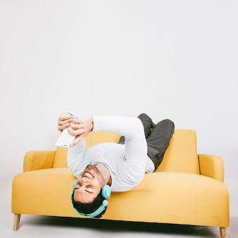Glücklicher junger mann auf dem sofa mit telefon und kopfhörer