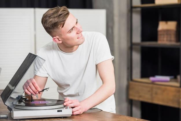 Glücklicher junger mann beim auf dem tisch den plattenspieler-vinylaufzeichnungsspieler weg schauen