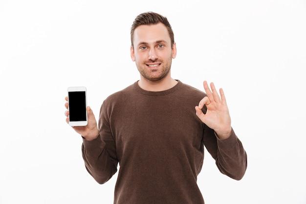 Glücklicher junger mann, der anzeige des handys zeigt