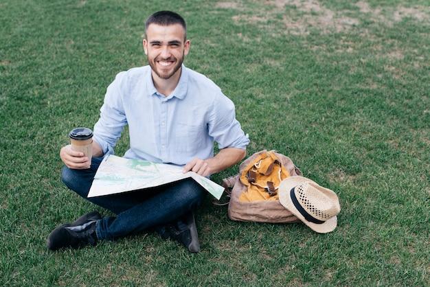 Glücklicher junger mann, der auf gras mit dem halten der wegwerfkaffeetasse und der karte sitzt