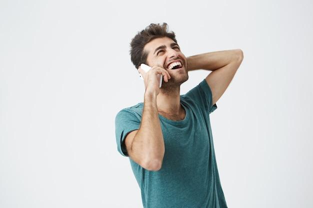 Glücklicher junger mann, der aufgeregt, glücklich und lachend fühlt, während er am telefon spricht. stilvoller hipster, der mit seiner freundin über smartphone mit lächeln kommuniziert