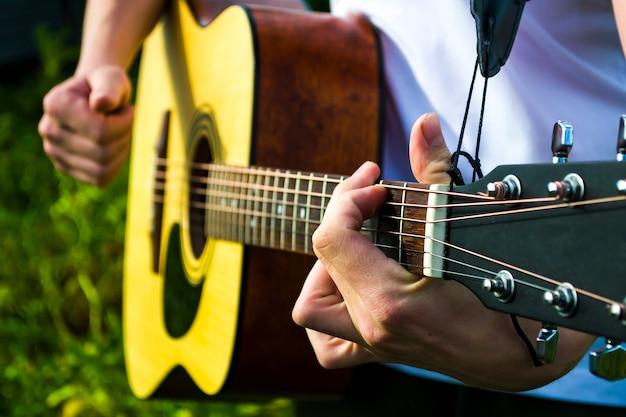 Glücklicher junger mann, der außerhalb des hauses gitarre spielt