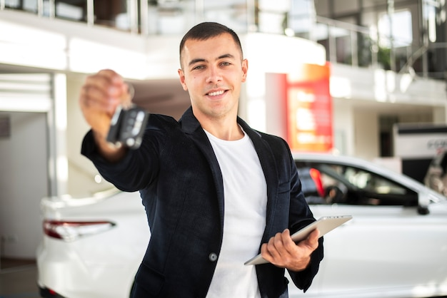 Glücklicher junger mann, der autoschlüssel hält