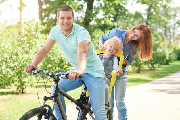 Glücklicher junger mann, der beim radfahren mit seinem kind in einem babyfahrradsitz und seiner schönen frau am örtlichen park auf einem aktiven sommertagfamilien-aktiven lebensstilkonzept lächelt.