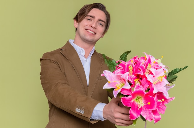 Glücklicher junger mann, der blumenstrauß hält, der fröhlich lächelt, um mit internationalem frauentagskonzept zu gratulieren, das über grüner wand steht