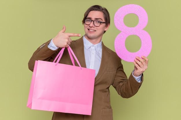 Glücklicher junger mann, der brillen hält, die papiertüten mit geschenken und nummer acht aus pappe halten, die mit zeigefinger darauf zeigt lächelndes internationales frauentagsmarschkonzept