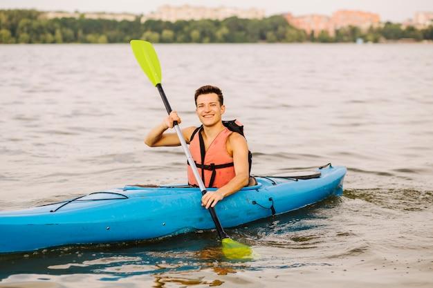 Glücklicher junger mann, der das paddel kayaking auf see verwendet