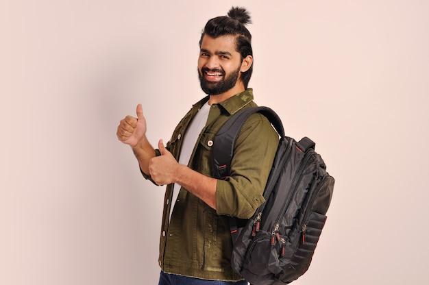 Glücklicher junger mann, der daumen mit beiden händen zeigt, die rucksack halten
