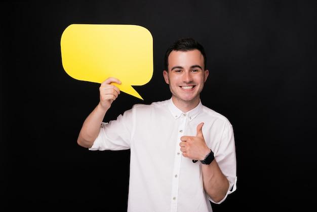 Glücklicher junger mann, der daumen oben zeigt und eine gelbe sprachblase auf schwarzem hintergrund hält. kommentar und like-konzept.