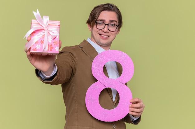 Glücklicher junger mann, der die brille hält, die nummer acht aus pappe und gegenwart hält und an der front lächelnd fröhlich internationalen frauentag steht über grüner wand steht