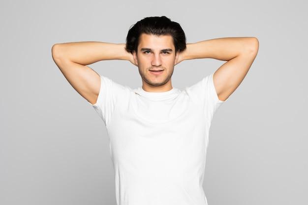 Glücklicher junger mann, der die hände hinter dem kopf hält und isoliert auf weiß aufschaut