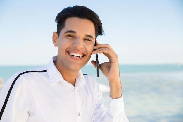 Glücklicher junger mann, der draußen um smartphone ersucht