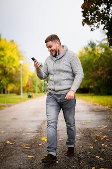 Glücklicher junger mann, der durch den park geht