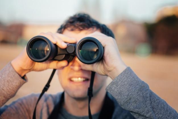 Glücklicher junger mann, der durch ferngläser während des sonnenuntergangs schaut