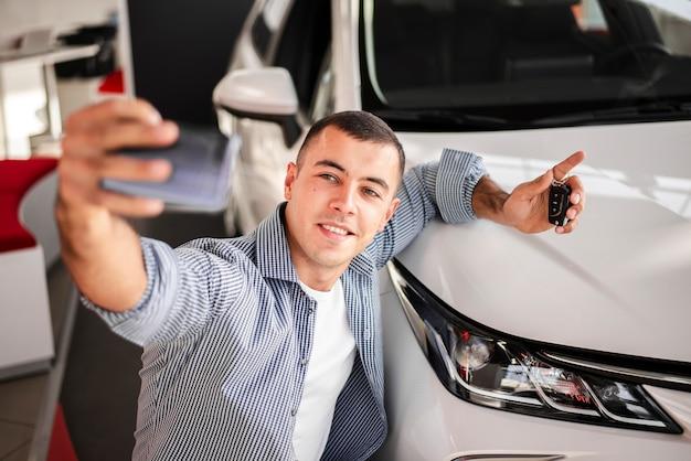 Glücklicher junger mann, der ein foto mit dem auto macht