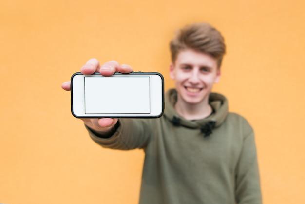 Glücklicher junger mann, der ein smartphone mit einem weißen bildschirm auf einer orange wand hält und lächelt.