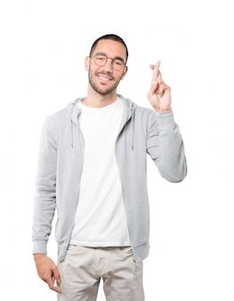 Glücklicher junger mann, der eine gekreuzte fingergeste tut