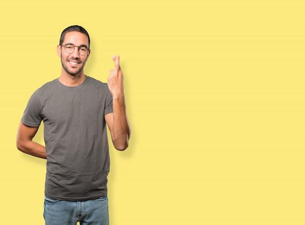 Glücklicher junger mann, der eine geste der gekreuzten finger tut
