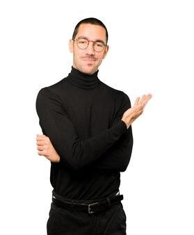 Glücklicher junger mann, der eine geste des rufens mit der hand macht