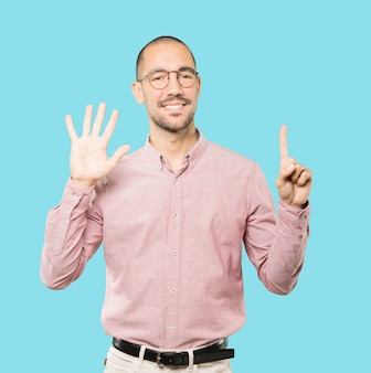 Glücklicher junger mann, der eine geste nummer sechs mit seinen händen tut