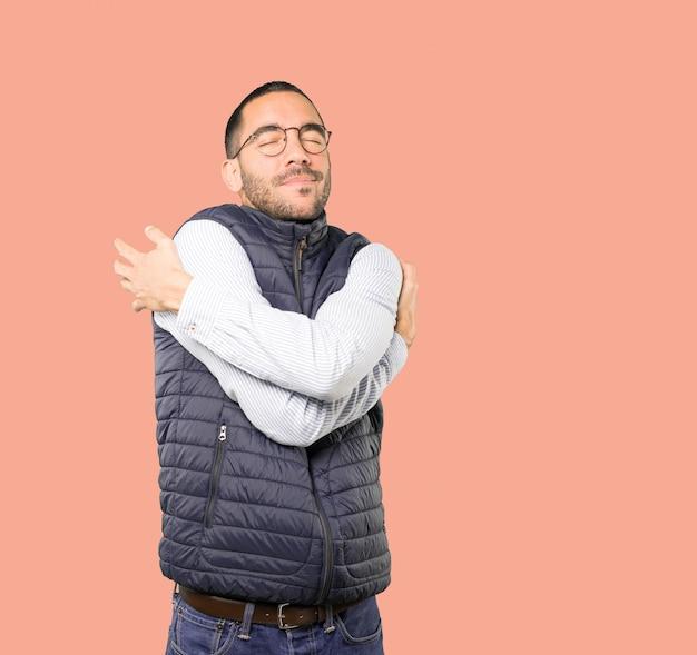 Glücklicher junger mann, der eine umarmungsgeste tut