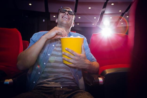 Glücklicher junger mann, der einen film 3d aufpasst