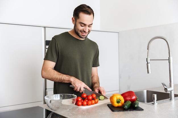 Glücklicher junger mann, der einen frischen salat macht, während er in der küche steht