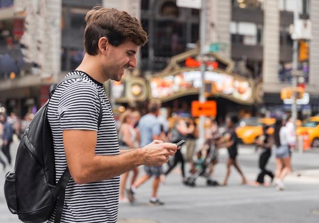 Glücklicher junger mann, der einen smartphone betrachtet