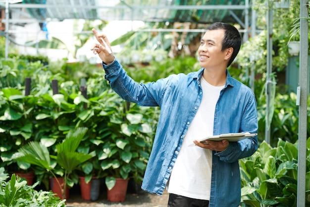 Glücklicher junger mann, der es genießt, in seinem gartencenter zu arbeiten, pflanzen zu überprüfen und notizen im dokument zu machen