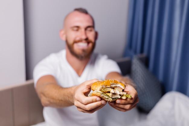 Glücklicher junger mann, der fastfood zu hause im schlafzimmer auf bett hat