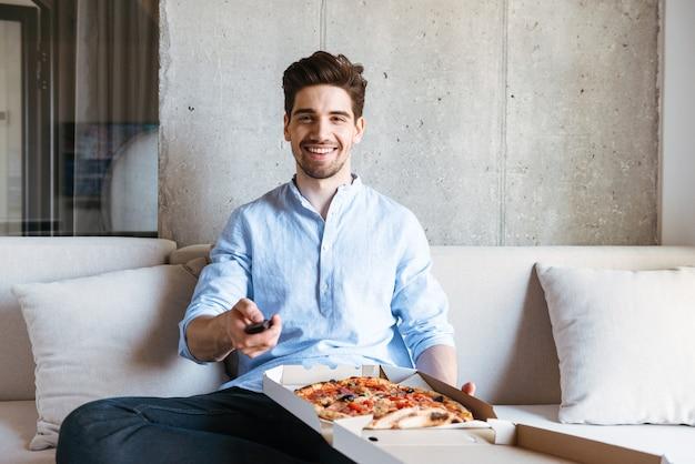 Glücklicher junger mann, der fernsehfernbedienung hält