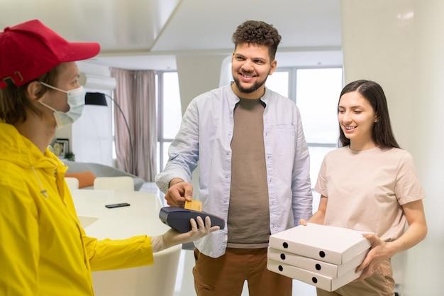 Glücklicher junger mann, der für pizza bezahlt, während er die kreditkarte über dem zahlungsterminal hält