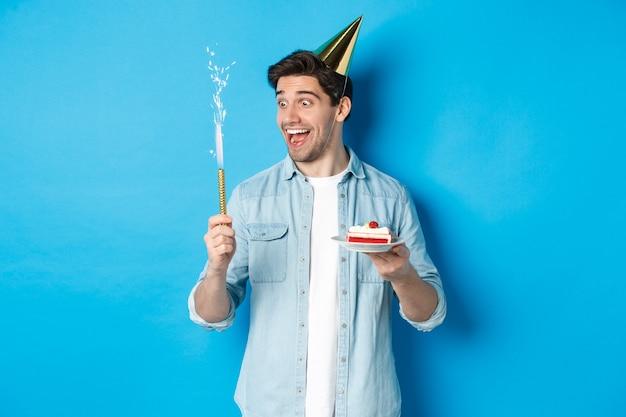 Glücklicher junger mann, der geburtstag im partyhut feiert, b-tageskuchen hält und lächelt, über blauer wand stehend