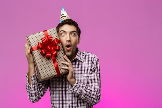 Glücklicher junger mann, der geburtstagsgeschenk im kasten über lila wand hält.