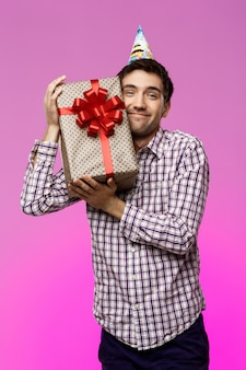 Glücklicher junger mann, der geburtstagsgeschenk im kasten über lila wand umarmt.