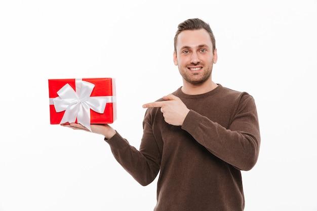 Glücklicher junger mann, der geschenkboxüberraschung hält.