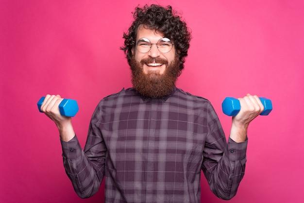 Glücklicher junger mann, der gewichte nahe rosa wand hält