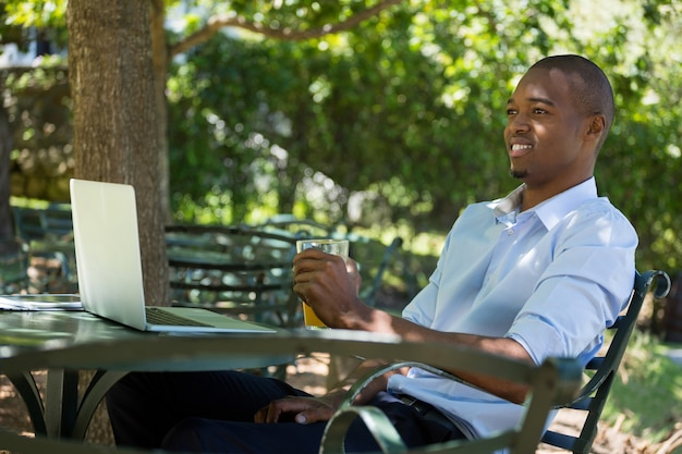 Glücklicher junger mann, der glas orangensaft am restaurant hält
