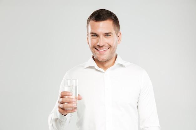 Glücklicher junger mann, der glas voll wasser hält.