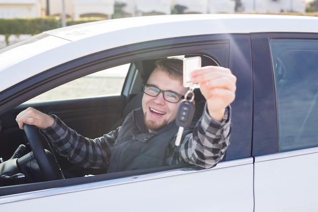 Glücklicher junger mann, der im auto sitzt und autoschlüssel hält