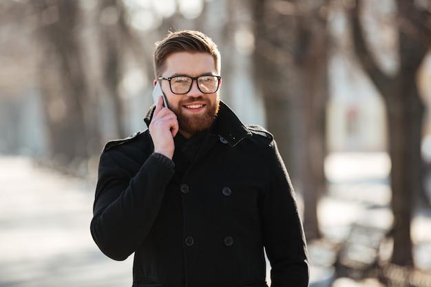 Glücklicher junger mann, der im winter auf handy draußen spricht