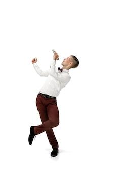 Glücklicher junger mann, der in freizeitkleidung oder anzug tanzt und legendäre bewegungen der berühmtheit aus der kulturgeschichte wieder herstellt