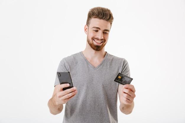 Glücklicher junger mann, der kreditkarte mit handy hält.