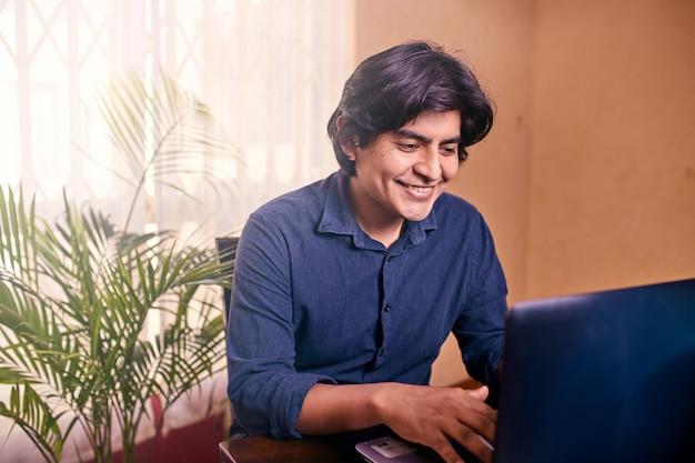Glücklicher junger mann, der laptop oder computer am schreibtisch benutzt.