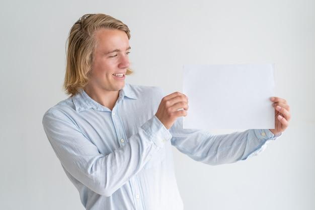 Glücklicher junger mann, der leeres blatt papier zeigt