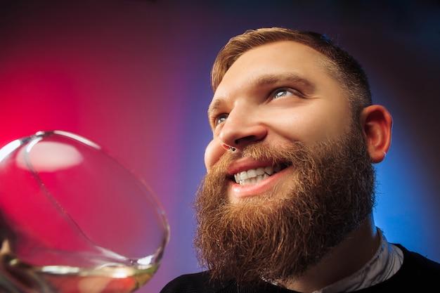 Glücklicher junger mann, der mit glas wein aufwirft. emotionales männliches gesicht. blick aus dem glas.