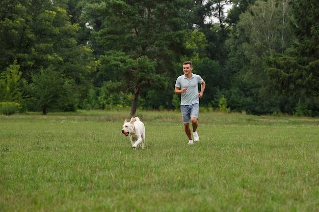 Glücklicher junger mann, der mit hund labrador draußen läuft